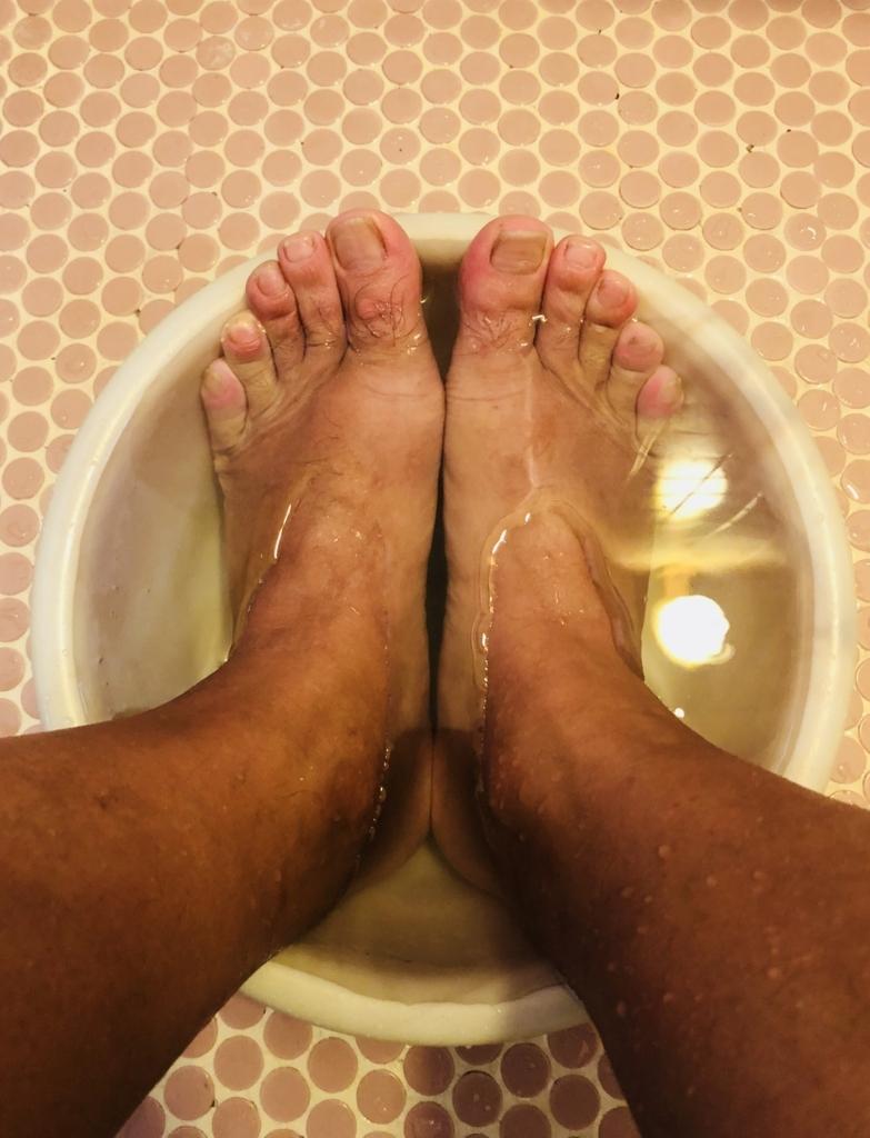 洗面器に重曹水を入れて足を浸けている