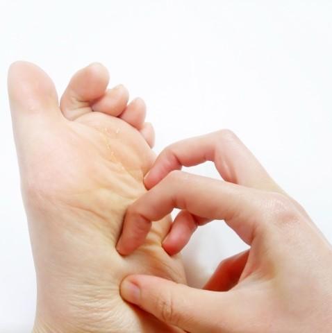 水虫の足の裏をかいている手