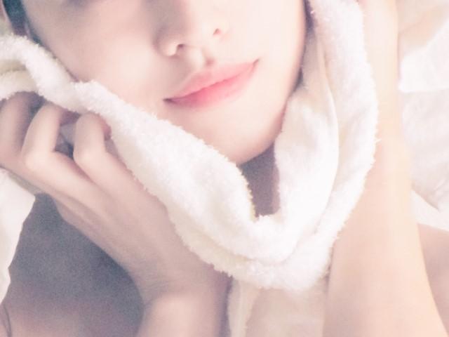 入浴後にタオルで顔を拭く女性