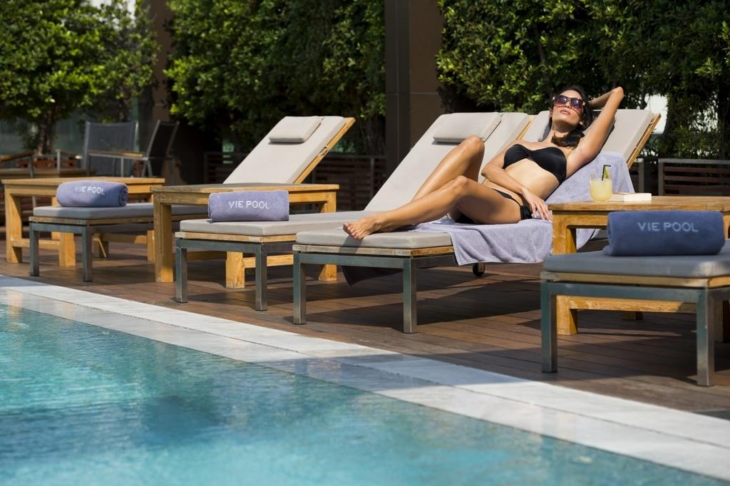 静かなホテルのプールサイドで横たわる女性