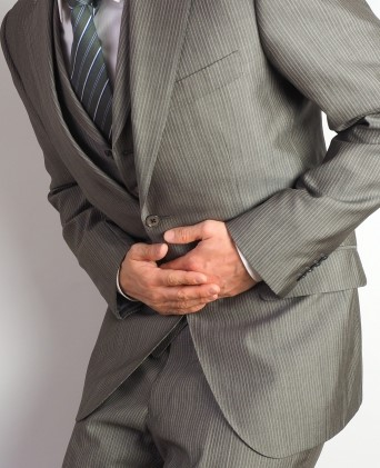 胃潰瘍で胃を抑える男性
