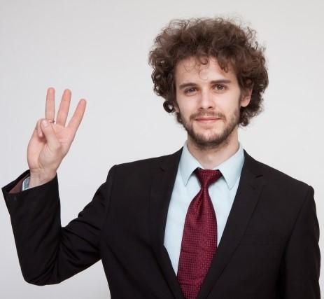 指を3本立てる男性