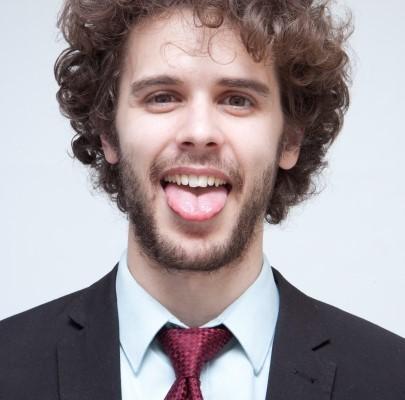 舌をだして舌苔を見せる男性
