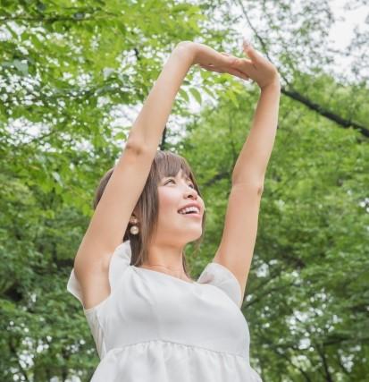 木の下で気持ちよく背伸びをする女性