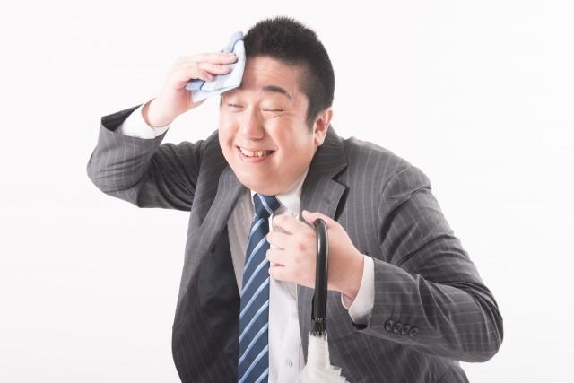 洗顔シートで汗を拭く男性