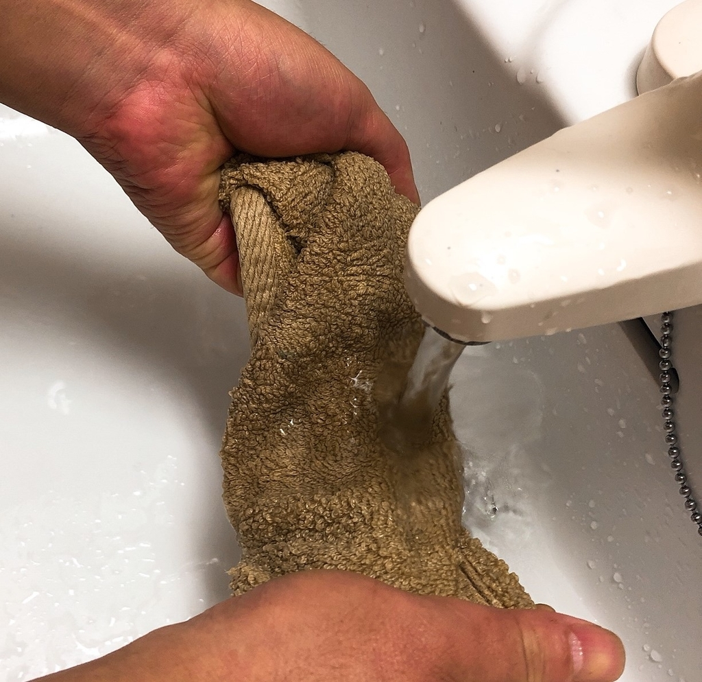 使ったタオルを洗面所で洗っている