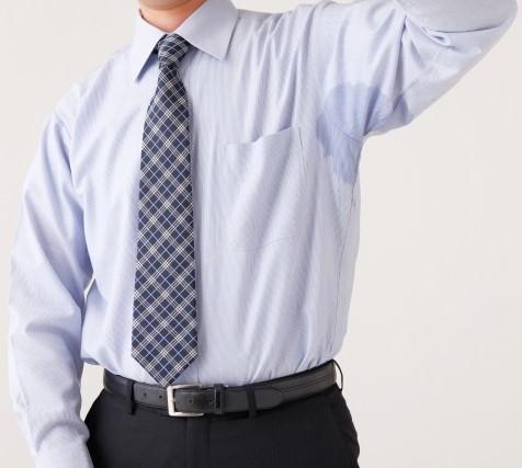 脇の汗ジミが浮かんだYシャツを着た男性