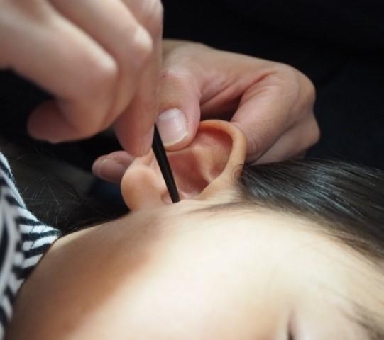 子供の耳垢掃除をする親