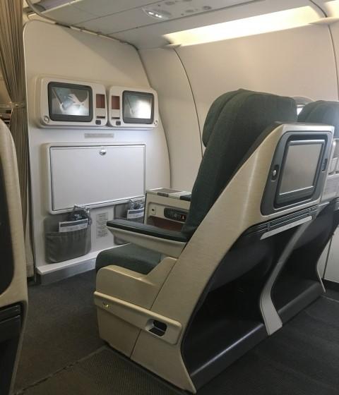 機内エンターテイメントのモニター画面と広い座席