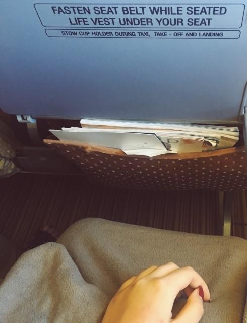 機内で毛布を膝にかけている人
