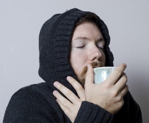 寒そうにお茶を飲む冷え性男性
