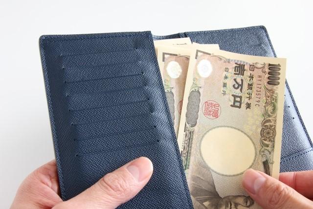 財布から一万円札を出して脱毛費用を払う男の手
