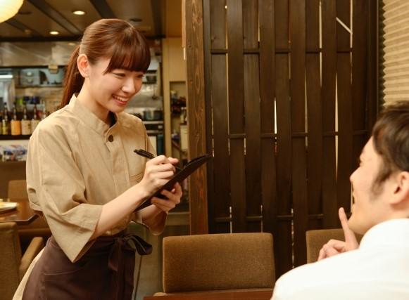 居酒屋で客のオーダーをとる、接客中の女性スタッフ