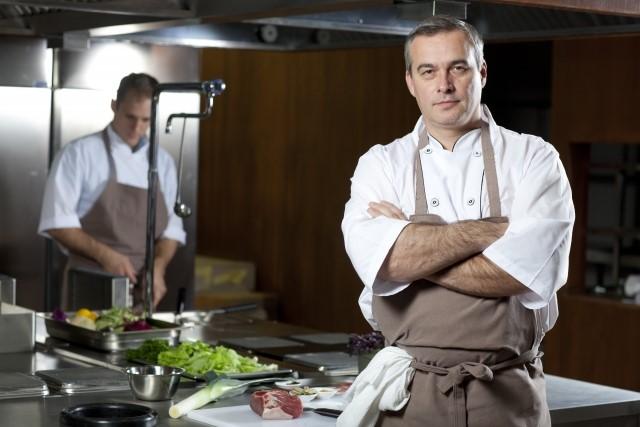 厨房内で調理をするスーシェフと、腕を組むシェフ