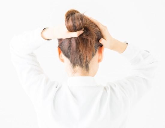 ロングヘアーを後ろでまとめようとしている女性