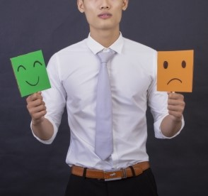笑顔としかめっ面のイラストプラカードを持つ人