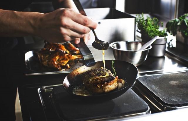 店のキッチンでフライパンで肉を調理する人