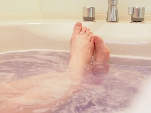 脚を浴槽内で伸ばした入浴中の女性