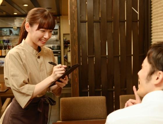 魅力的な笑顔で接客をする飲食店バイト