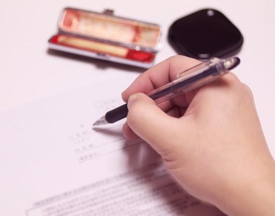 同意書に署名捺印する親