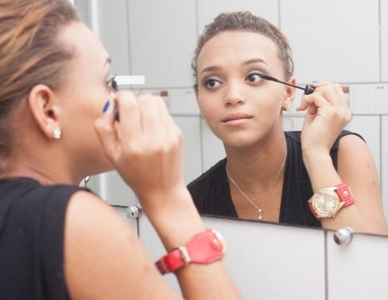 鏡を見てメイクをする飲食店バイトの女性