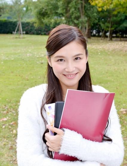 ノートを抱えてキャンパスの庭に立つ美人な女子大学生
