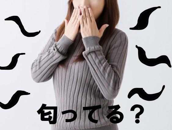 鼻と口を抑える匂いを気にする飲食店バイトの女性