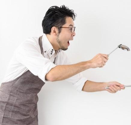 私服の上にエプロンをつけて働くキッチンスタッフの男性