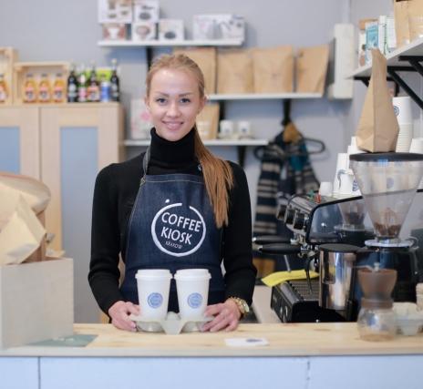 私服の上にエプロンをつけて働くカフェの女性バイト