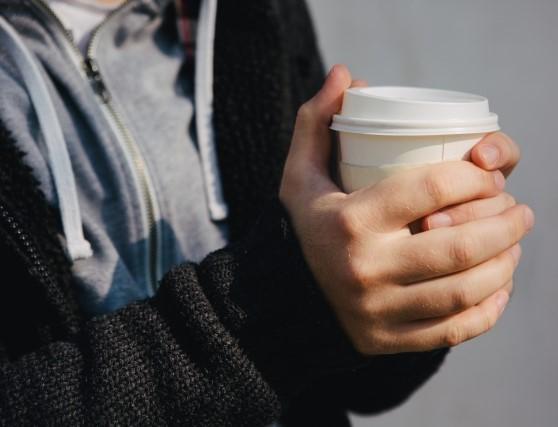 テイクアウトコーヒーを持って休憩する男性