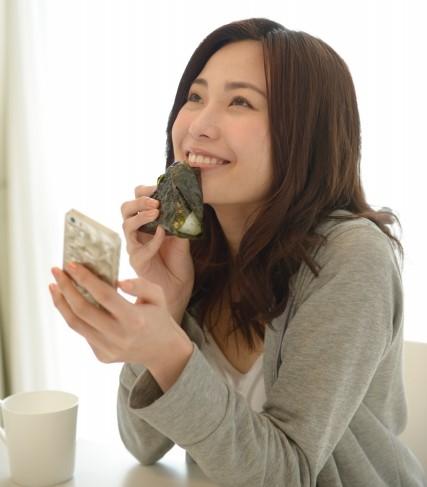 休憩時間におにぎりを食べながらスマホをチェックする女性