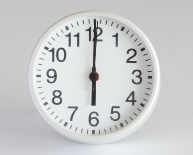 6時を指すアナログの壁掛け時計
