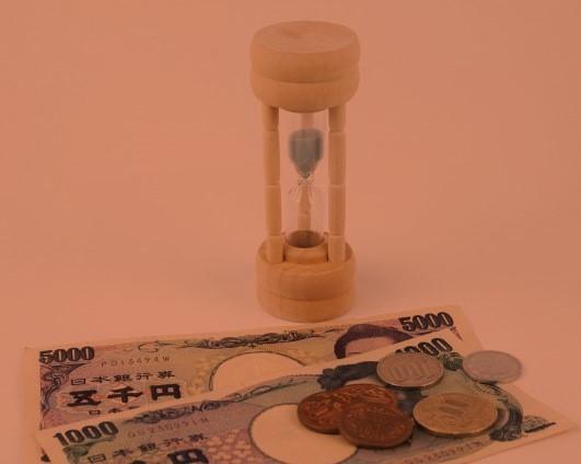 お金(お札と小銭)の後ろに砂時計。背景夕方