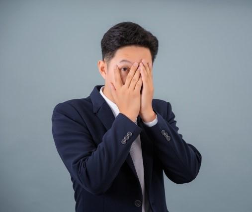 顔を隠した手の指の間からこちらを見る恥ずかしいと思っている男性