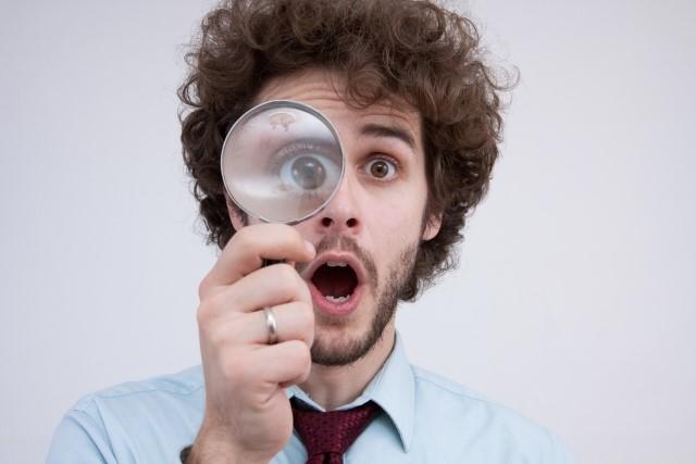 虫眼鏡を持って確認する男性