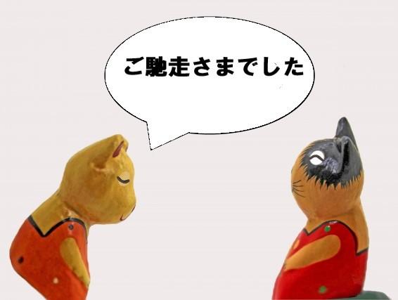 ご馳走さまでした、とお辞儀をする猫の人形