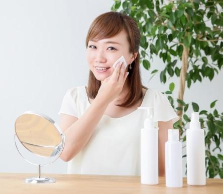コットンを使って収れん化粧水を塗る女性