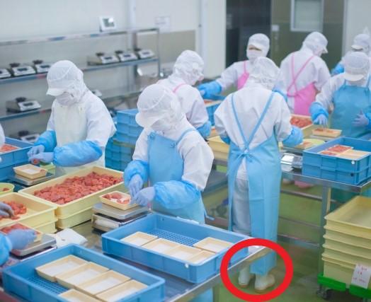 白いコックシューズを履いている食品工場内の作業員