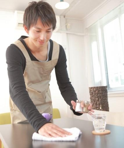 テーブルを拭く飲食店バイトが楽しくて仕方ない男性