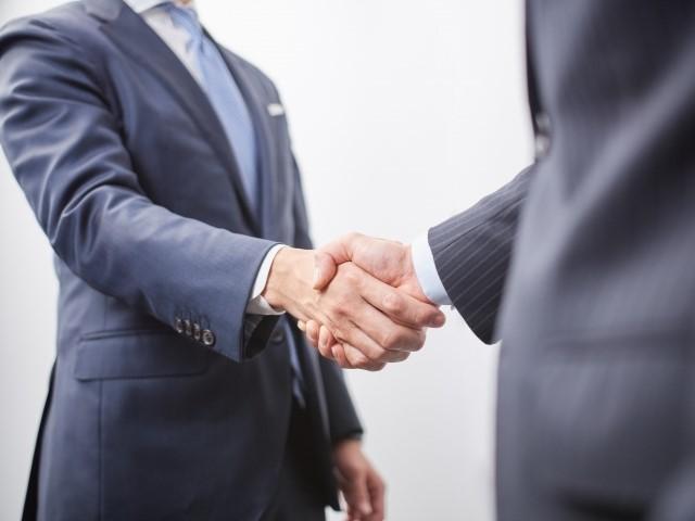 転職先が決まって握手をするビジネスマン