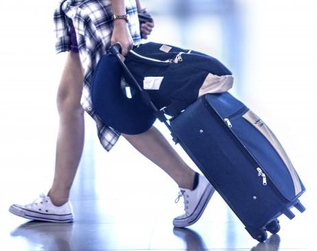 キャリーバッグを引いて短期リゾートバイトに向かう女性