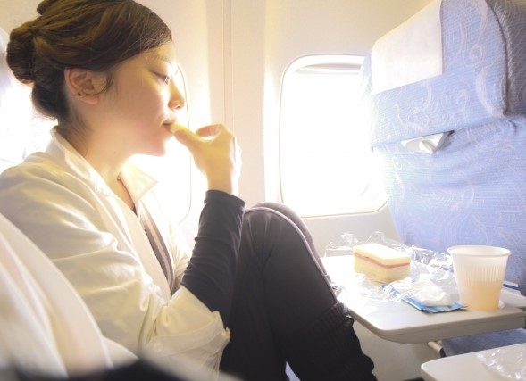 飛行機でリゾートバイト先に向かう女性