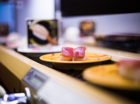 回転寿司のカウンター席で流れてくるマグロ