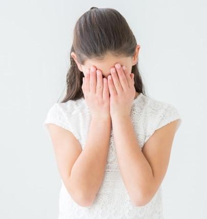 両手で顔をかくすストカー被害に悩む女子高生