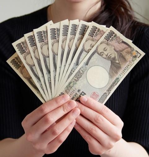 10万(1万円札10枚)を胸元で扇子のように広げる女性