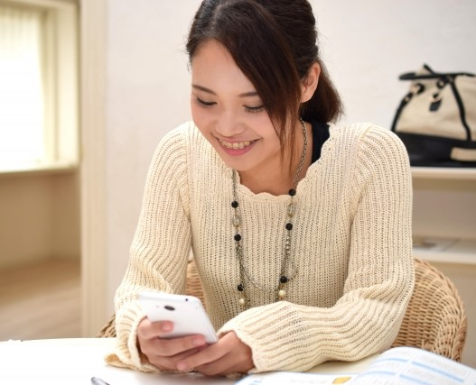 スマホでweb応募のメール送信をする女性