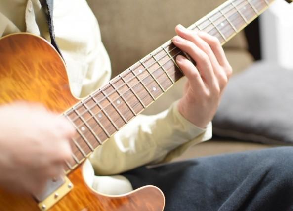 買取に出したいギターをソファーで弾く男性