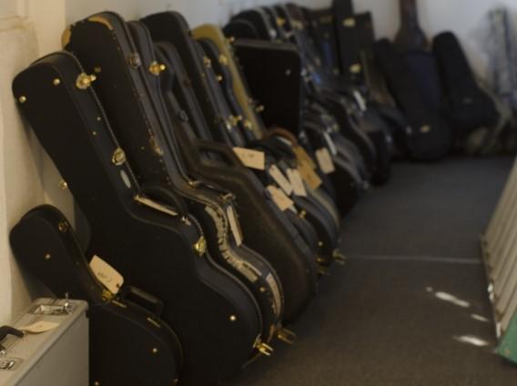 法人の事務所にある大量に置かれたケースに入ったギター