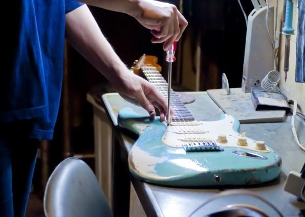 壊れたギターを修理している男性