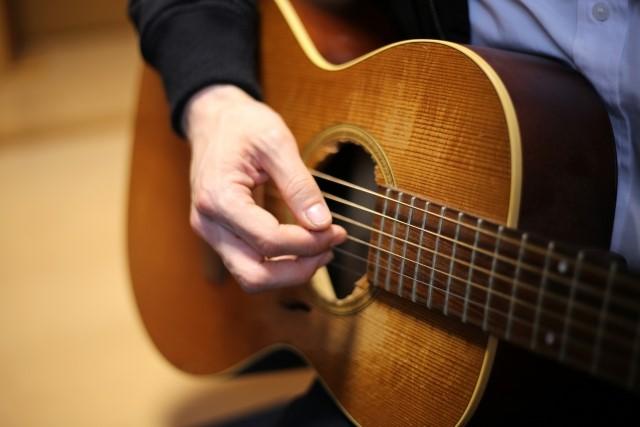 所沢市で捨てるアコースティックギターを弾く男性